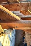 Il lavoratore torce la barra dello scaffale facendo uso di una chiave immagini stock