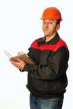 Il lavoratore in un casco arancio scrive in un taccuino Fotografie Stock