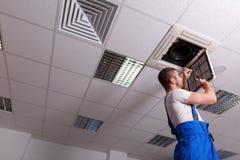 Il lavoratore in uniforme del blu taglia i cavi da ventilazione Immagini Stock Libere da Diritti