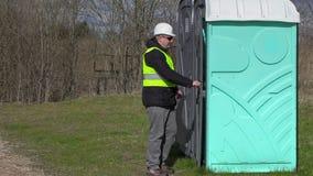 Il lavoratore va nella toilette portatile archivi video