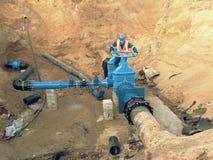 Il lavoratore in vestiti della sicurezza guida il condotto della valvola sul tubo di acqua potabile della città Fotografia Stock Libera da Diritti
