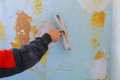 Il lavoro allinea Mettendo gesso sulla parete con la spatola Fotografia Stock