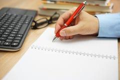 Il lavoro d'ufficio, uomo d'affari che la mano è scrive in un taccuino con il libro Fotografie Stock Libere da Diritti