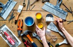 Il lavoro del costruttore con i mezzi di riparazione professionali ha messo sulla vista superiore del fondo di legno Immagini Stock