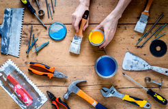 Il lavoro del costruttore con i mezzi di riparazione professionali ha messo sulla vista superiore del fondo di legno Immagine Stock