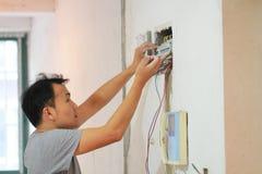 Il lavoro di ristrutturazione elettrico, uomo installa il materiale elettrico industriale fotografia stock libera da diritti
