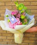Il lavoro di un fiorista in un negozio di fiore - un mazzo luminoso con una cartolina d'auguri Immagine Stock