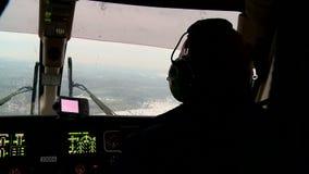 Il lavoro di un pilota dell'elicottero nella cabina di pilotaggio nell'inverno video d archivio