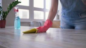 Il lavoro domestico, la ragazza in guanti con la bottiglia del detersivo ed il panno in sue mani pulisce la tavola in cucina stock footage