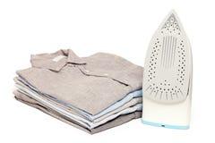 Il lavoro domestico rivestente di ferro rivestito di ferro ha piegato il fondo bianco pulito delle camice fotografia stock