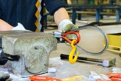 Il lavoro mette il gancio del carico nel ciclo dell'imbracatura d'acciaio Fotografie Stock Libere da Diritti