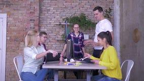 Il lavoro quotidiano, personale amichevole di affari che si dà alti cinque si siede alla tavola e fa le note in un taccuino e video d archivio