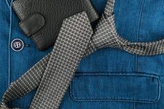 Il legame ed il portafoglio grigi si trovano sul rivestimento del denim Fotografia Stock