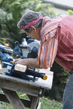 Il legno di sawing dell'uomo con lo scivolamento del mitra composto ha visto Fotografia Stock