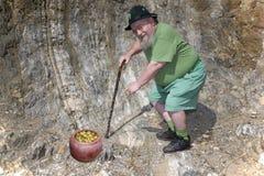Il Leprechaun indica il suo POT di oro tradizionale Fotografia Stock