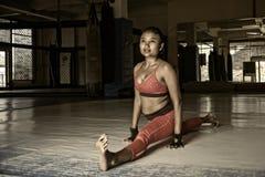 Il lerciume duro pubblica di giovane donna asiatica sudata in vestiti di sport che allungano e gambe di spaccatura per i muscoli  Immagini Stock Libere da Diritti