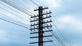 Il lerciume Palo elettrico ad alta tensione con molto cavo allinea su cielo blu e sulla nuvola bianca Immagine Stock