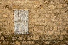 Il lerciume Weathered ha chiuso la finestra in vecchia parete di pietra abbandonata della casa immagini stock