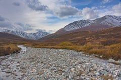 Il letto del fiume e delle montagne innevate nella caduta Fotografia Stock
