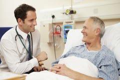 Il letto del paziente del dottore Sitting By Male in ospedale immagine stock libera da diritti