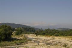 Il letto di fiume del fiume e delle colline pedemontana della montagna Immagini Stock Libere da Diritti