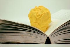 Il libro aperto con giallo ha sgualcito la palla di carta su fondo scuro Fotografia Stock