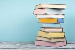 Il libro aperto, impilante, libro con copertina rigida prenota sulla tavola e sul fondo di legno Di nuovo al banco Copi lo spazio Fotografia Stock