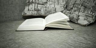 Il libro aperto si trova su un sofà vicino ai cuscini Fotografie Stock