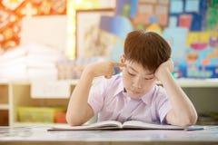Il libro di lettura asiatico felice del bambino e pensa a tale proposito Immagine Stock Libera da Diritti