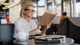 Il libro di lettura attraente di signora di affari maturi durante il pranzo irrompe il caffè video d archivio