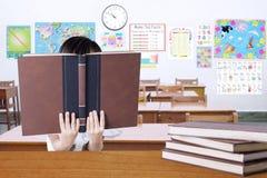 Il libro di lettura del bambino e copre il suo fronte Fotografia Stock Libera da Diritti