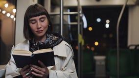 Il libro di lettura del passeggero o della giovane donna che si siede nel trasporto pubblico, steadicam ha sparato Movimento lent stock footage