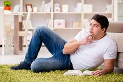 Il libro di lettura dell'uomo a casa sul pavimento Immagini Stock