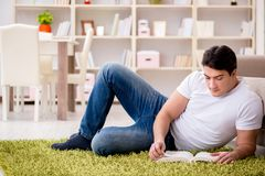 Il libro di lettura dell'uomo a casa sul pavimento Fotografie Stock Libere da Diritti