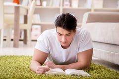 Il libro di lettura dell'uomo a casa sul pavimento Fotografia Stock