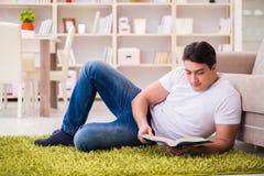 Il libro di lettura dell'uomo a casa sul pavimento Immagini Stock Libere da Diritti