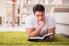 Il libro di lettura dell'uomo a casa sul pavimento Immagine Stock Libera da Diritti