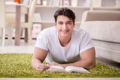 Il libro di lettura dell'uomo a casa sul pavimento Fotografie Stock