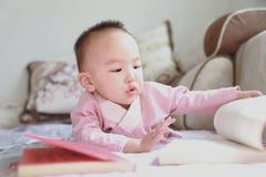 Il libro di lettura della neonata si riposa sul sofà immagine stock libera da diritti