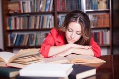 Il libro di lettura della ragazza nella biblioteca sta preparando per gli esami Fotografie Stock Libere da Diritti