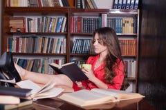 Il libro di lettura della ragazza nella biblioteca sta preparando per gli esami Fotografia Stock Libera da Diritti