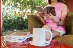 Il libro di lettura e mangiare il tè caldo è il suo gusto favorito immagine stock