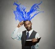 Il libro di lettura premuroso dell'uomo d'affari variopinto spruzza uscire dalla testa Fotografie Stock