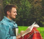 Il libro di lettura sorridente del giovane all'aperto con un plaid rosso caldo e una tazza di tè sull'autunno del fondo vacations fotografie stock