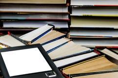 Il libro elettronico con uno schermo bianco si trova dei sui libri colorati multi aperti che si trovano su un fondo scuro, primo  immagine stock