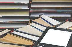 Il libro elettronico con uno schermo bianco si trova dei sui libri colorati multi aperti che si trovano su un fondo scuro, primo  fotografia stock