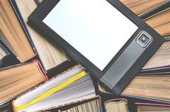 Il libro elettronico con uno schermo bianco si trova dei sui libri colorati multi aperti che si trovano su un fondo scuro, primo  immagini stock libere da diritti