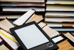 Il libro elettronico con uno schermo bianco si trova dei sui libri colorati multi aperti che si trovano su un fondo scuro, primo  fotografie stock