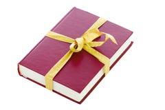 Il libro rosso in un imballaggio del regalo isolato su un bianco Fotografia Stock