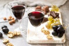 Il liquore casalingo di Creme de Cassis è servito con l'uva, i dadi ed il cioccolato Stile rustico fotografia stock libera da diritti